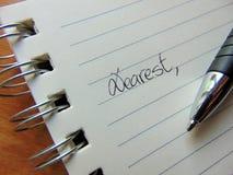 Écrivant une lettre sur le papier rayé commençant par cher, image stock