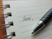 Écrivant une lettre sur le papier rayé commençant par cher, photographie stock libre de droits