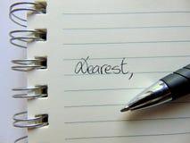 Écrivant une lettre sur le papier rayé commençant par cher, photographie stock