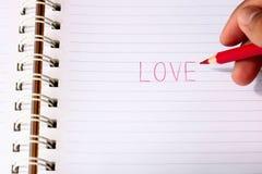 Écrivez l'amour de mot avec le crayon rouge dans des mains du ` s d'homme de tache floue Image stock