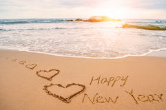 Écrivez la bonne année sur la plage avec des coeurs Photo stock