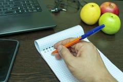 Écrivez les idées dans un carnet avec un stylo, ordinateur portable, photographie stock libre de droits