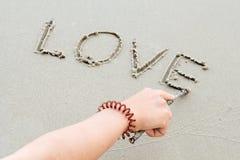 Écrivez les lettres d'amour de mot sur le sable Image stock