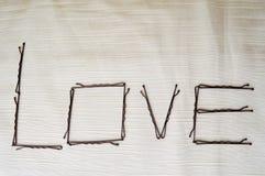 Écrivez un amour écrit par des épingles à cheveux-ignoramuses sur un fond beige Image libre de droits