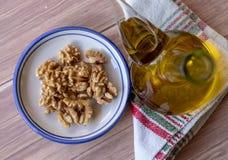 Écrous épluchés sains d'un plat en céramique accompagné d'une bouteille d'huile d'olive vierge supplémentaire Vue supérieure photos stock