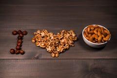 Écrous d'amour de l'inscription I, des écrous, des noix, des amandes et des noisettes et des tasses d'un blanc avec des écrous Image stock