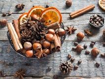 Écrous d'ingrédients d'hiver, cônes, oranges, anis d'étoile de cannelle dans une cuvette Type rustique Photographie stock libre de droits
