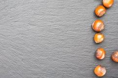 Écrous de noisette Vue supérieure sur un plat d'ardoise Copiez l'espace du côté gauche images libres de droits