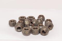 Écrous en métal et d'acier sur le fond blanc Photographie stock