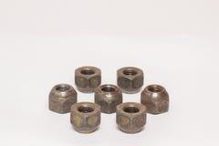 Écrous en métal et d'acier sur le fond blanc Photographie stock libre de droits