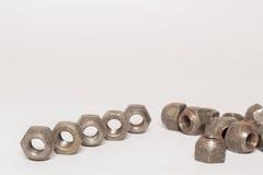 Écrous en métal et d'acier sur le fond blanc Photo libre de droits