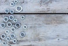 Écrous en métal sur le fond en bois Écrous filetés inoxydables de construction sur le concept de construction de panneau en bois  Image stock