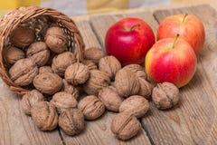 Écrous et pommes jaunes rouges sur un fond en bois Image stock