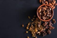 Écrous et raisins secs au fond noir Source saine de graisse pour des vegans et des végétariens Photo stock