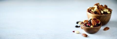 Écrous et raisins secs mélangés dans la cuvette en bois Nourriture et casse-croûte sains Noix, pistaches, amandes, noisettes, ana photo libre de droits