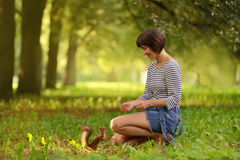 Écureuil de alimentation de jeune femme avec une noisette Image libre de droits