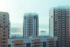 Édifices hauts dans le brouillard à l'aube dans la ville Photographie stock libre de droits
