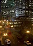 Édifices hauts et circulation du centre de nuit Photographie stock libre de droits