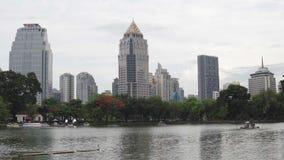 Édifices hauts sur le bord de mer du lac de ville dans le centre ville Scène calme : ondulations sur la surface d'étang, catam banque de vidéos