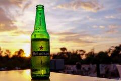 Édition de ville de bière de Heineken sur la table pendant le coucher du soleil Photographie stock libre de droits