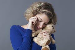 Édredon affectueux de caresse de la fille 20s bouleversée pour se détendre Image stock