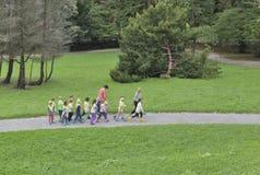 Éducateurs avec un groupe d'enfants préscolaires en parc Image libre de droits