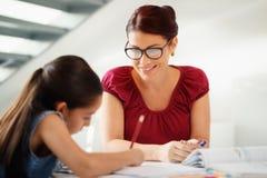 Éducation avec la fille de aide de maman faisant des devoirs d'école à la maison photographie stock