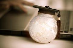 Éducation dans global, chapeau d'obtention du diplôme sur le modèle supérieur Asi de globe de la terre image libre de droits