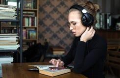 Éducation des adultes, étudiant dans des écouteurs fonctionnant dans la bibliothèque ou salle de classe d'université photo stock