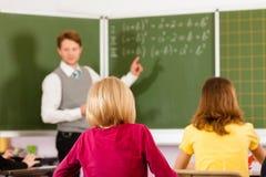 Éducation - professeur avec l'élève dans l'enseignement d'école Image libre de droits