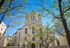 Église avec les dômes d'or à la lumière du soleil parmi des arbres photo libre de droits