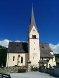 Église avec un clocher et horloges là-dessus le jour ensoleillé avec un ciel bleu et des nuages sur le fond Photo libre de droits