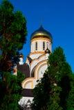 Église blanche chrétienne au jour d'été ensoleillé et aux arbres de thuja photo stock