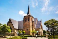 Église catholique Sint-Martinuskerk dans Houthalen-Helchteren, Belgique Homme sur une bicyclette Photographie stock