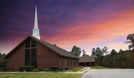 Église de pays de style de carlingue de rondin au coucher du soleil Image stock