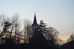Église derrière la forêt après coucher du soleil photo libre de droits