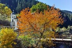 Église du 19ème siècle de l'hypothèse, de la rivière et de l'arbre d'automne dans la ville de Shiroka Laka, Bulgarie Image libre de droits