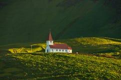 Église en bois sur la colline verte au lever de soleil, Vik, Islande Photographie stock