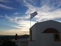 Église grecque et drapeau avec le ciel photographie stock
