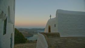 Église grecque et seaview sur le coucher du soleil photos stock