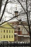Église orthodoxe, avec des murs rouges et un dôme, pendant chutes de neige Photo stock