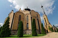 Église orthodoxe moderne avec des dômes construits de la brique Grande porte à côté de tour de cloche Photo libre de droits