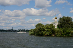 Église orthodoxe sur une île de rivière, et bateau de navigation Photo libre de droits