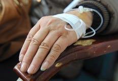 Égouttement dans une main de patients Photo stock