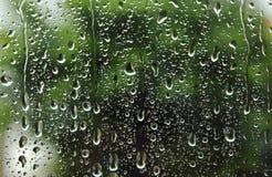 Égouttement en bas des gouttes de pluie sur le verre Photos libres de droits