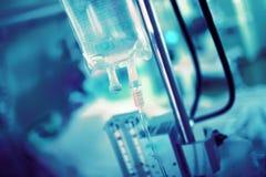 Égouttement IV sur le fond de l'équipement et du patient brouillés d'hôpital dans le lit image stock