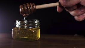 Égoutture de miel, versant du plongeur de miel dans le pot Plan rapproch? Plongement épais de miel banque de vidéos