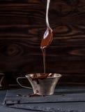 Égoutture liquide de chocolat de cuillère dans la tasse Photos stock