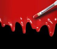 Égoutture rouge de peinture sur le noir Photo stock