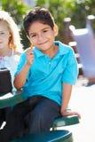 Élève élémentaire se reposant au Tableau mangeant le déjeuner Photo stock